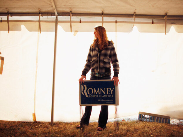 A young Mitt Romney supporter holds yard signs Thursday at a campaign event at J's Homestyle Cooking in Cedar Falls, Iowa.
