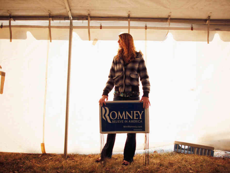 A young Mitt Romney supporter holds yard signs Thursday at a