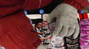 A volunteer arranges buttons before Mitt Romney speaks Wednesday in Clinton, Iowa.