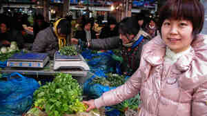 Anna Hu at the Ao Hua Farmers Market in Shanghai. After years of working long hours and eating only in restaurants, Hu has learned how to cook vegetables and eat more healthfully.
