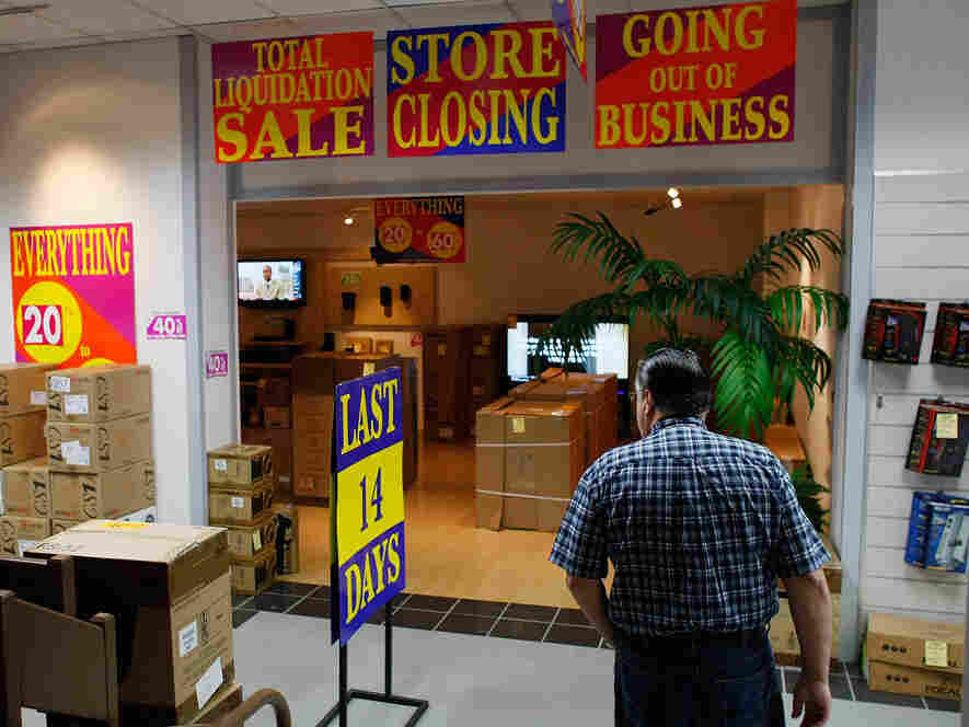 A shopper looks for bargains at an electronic store holding a going-out-of-business sale.