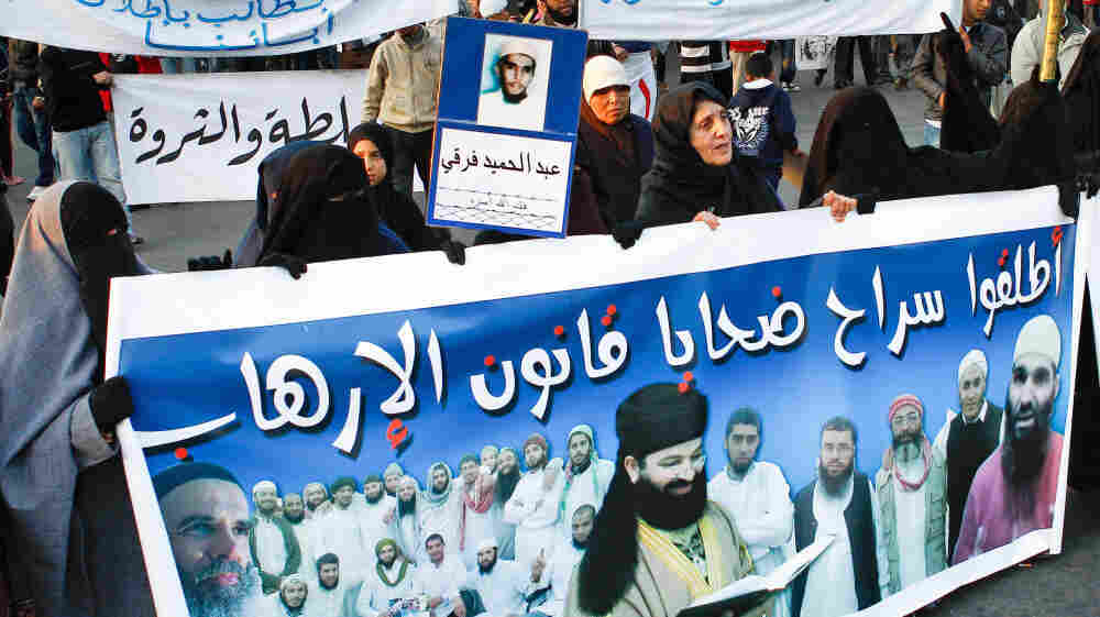 """Anti-government protesters shout as they carry a banner with portraits of several prisoners during a rally organized by the Moroccan Arab Spring movement in Casablanca on Dec. 25. The banner reads, """"We demand the release of all prisoners because of anti-terror laws."""""""