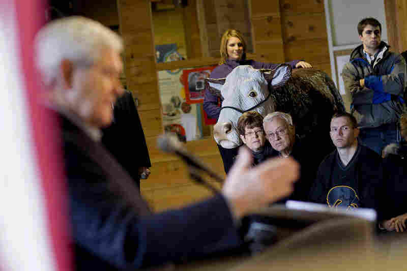 People watch as former House Speaker Newt Gingrich speaks during a campaign stop, Monday in Independence, Iowa.