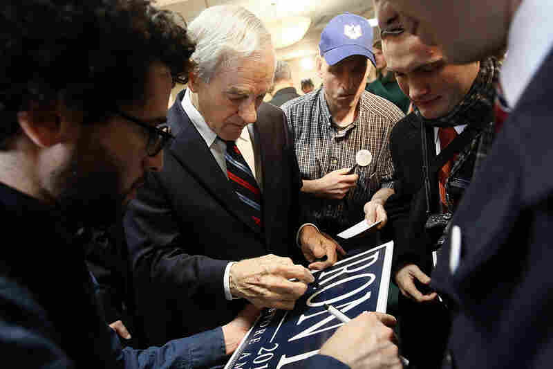 """U.S. Rep. Ron Paul of Texas signs autographs for supporters after a campaign event during his """"Whistle-stop"""" tour at the Steeple Gate inn Monday in Davenport, Iowa."""