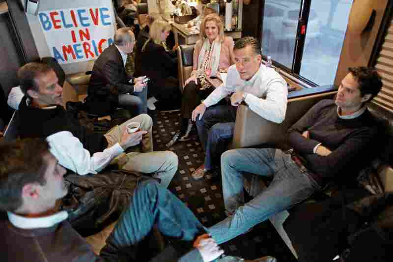 Romney sits with family members and South Dakota Sen. John Thune (second left) on his campaign bus after a rally at in Davenport on Monday.