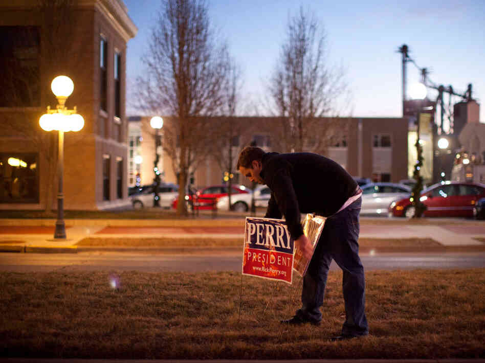 A supporter of Texas governor Rick Perry places campaign signs outside the Hotel Pattee before an event on Monday in Perry, Iowa.