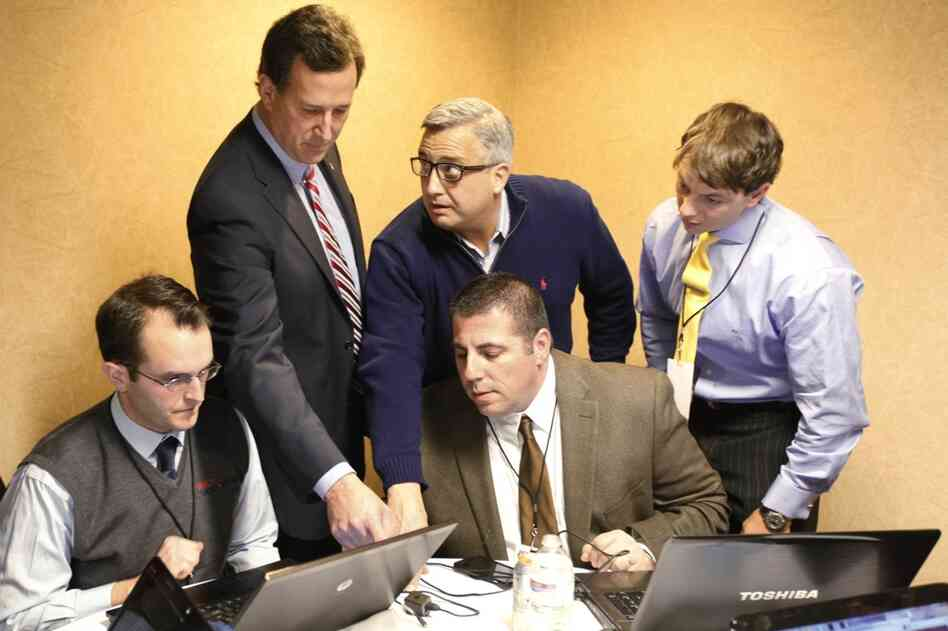 Rick Santorum (second from left) looks over caucus returns with campaign staff in his hotel room in Johnston.