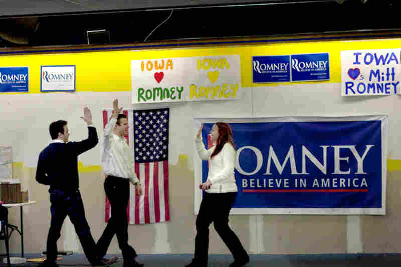 Mitt Romney volunteers throw high-fives at the campaign headquarters in Des Moines, Iowa, after a good event turnout.