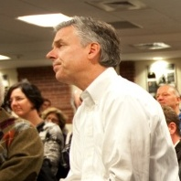 Huntsman (at left in white shirt) listened to an introduction by his wife, Mary Kaye, before speaking in Dover, N.H. Monday night. On the right are his son-in-law, Jeffrey Livingston, and his daughters Abby and Mary Anne.