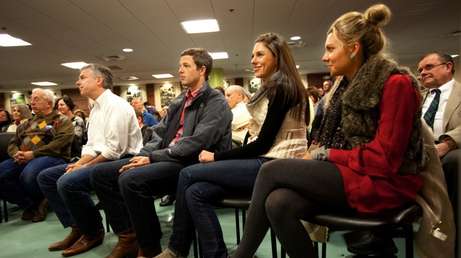 Huntsman (at left in white shirt) listened to an introduction by his wife, Mary Kaye, before speaking in Dover, N.H. Monday night. On the right are his son-in-law, Jeffrey Livingston, and his daughters Abby and Mary Anne.  (NPR)