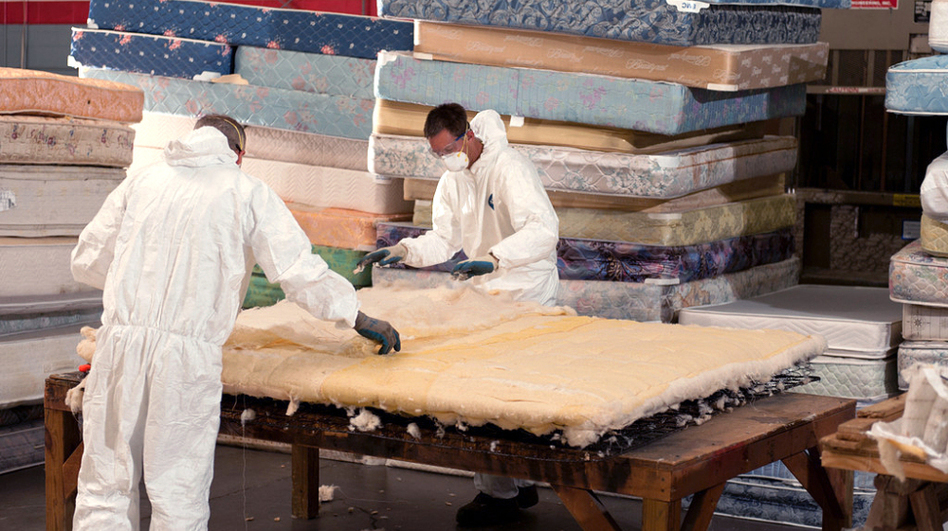 Men dismantle a mattress into reusable parts at the Spring Back recycling project in Nashville, Tenn.