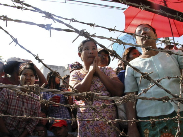 People stand behind barricades as they wait for family members to be freed from Insein Prison in Yangon, Myanmar, on Tuesday. Myanmar's government announced Monday that it is reducing the sentences of many prisoners, but stopped short of declaring an amnesty for political prisoners that many people had expected.