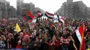 Syria's embattled President Bashar Assad still has supporters, particularly among his fellow Alawites, a minority who believe they will suffer if Assad is ousted. Here, Assad supporters rally Tuesday in the capital, Damascus.