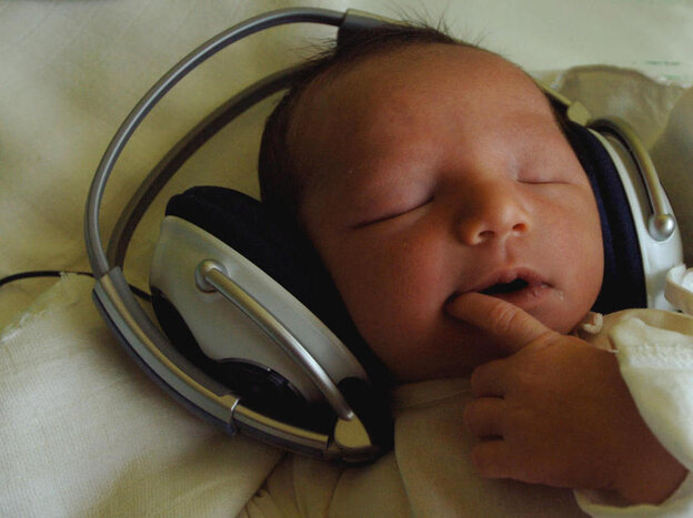 One-day-old Timea listens to music with headphones