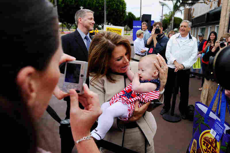 Bachmann holds 6-month-old Jane Morrissey as her mother, Heather Morrissey, snaps a photo at a rally in Costa Mesa, Calif., in September.