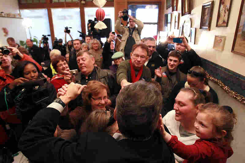 A curious toddler (far right) touches Texas Gov. Rick Perry while the presidential hopeful greets supporters at the Main Street Cafe in Council Bluffs, Iowa, in December.