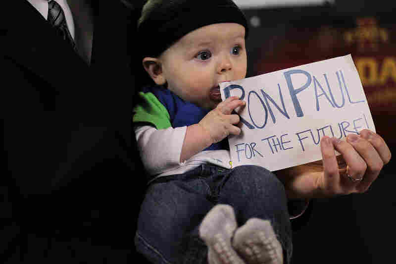 "An even younger Paul ""supporter,"" Raymond Landegent, holds a sign as he sits on his father's lap during a town hall meeting in Le Mars, Iowa."