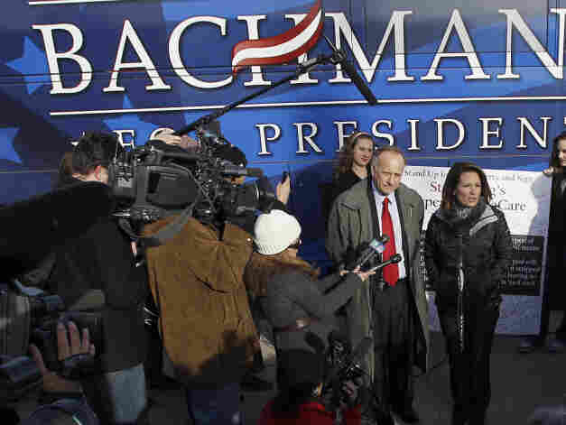 Republican presidential candidate Michele Bachmann (center) talks to the media after a campaign stop Tuesday at Valley High School in West Des Moines, Iowa.