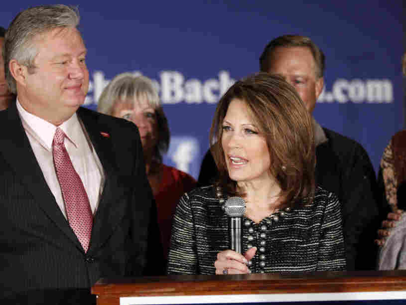 Minnesota Rep. Michele Bachmann, joined by husband Marcus (left) and family and friends, announces that she will end her campaign for president in West Des Moines on Wednesday.
