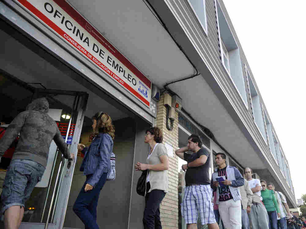 People wait in line at a government employment office in Madrid.