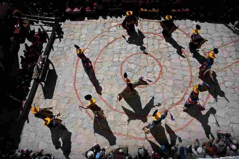 The tsowo, or head dancer and officiating monk of the Tiji festival, performs in the center of the sacred form of the mandala, while a ring of monks dance around him in one of the initial ceremonies.