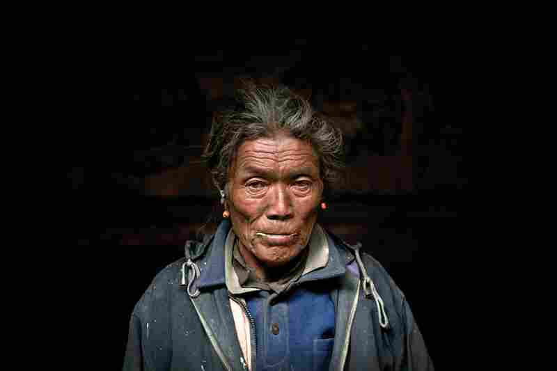 The winter monastery keeper stands for a portrait in the main hall of the monastery in Tetang.