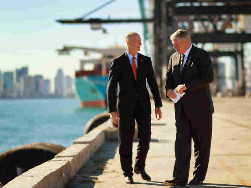 "Port of Miami Director Bill Johnson (right) speaks to Florida Gov. Rick Scott at the port. ""It is the game changer,"" Johnson says of the city's plan to deepen its port to accept new, larger ships from the Panama Canal."