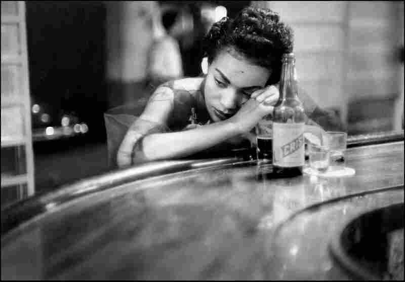 A girl sits at a brothel bar in Havana's red light district, 1954.