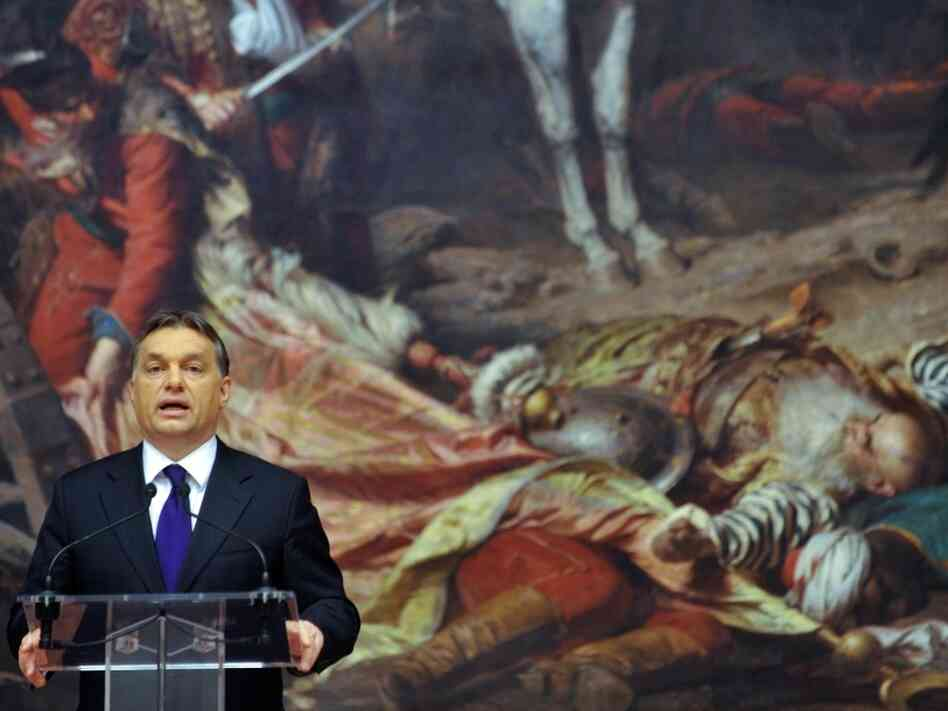Prime Minister Viktor Orban stands in front of a bloodbath.