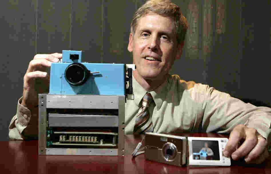 Steven J. Sasson shows the world's first digital camera (left), which he built in 1975, next to Kodak's EasyShare One, at Kodak headquarters in Rochester, N.Y., in 2005. The company is now trying to sell about a thousand patents for digital photography to prevent bankruptcy.