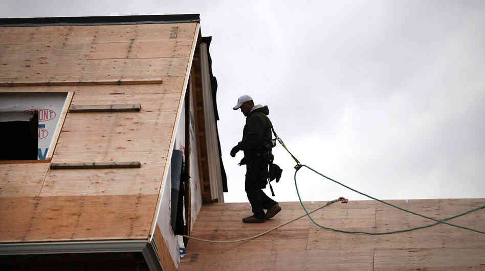 A construction worker walks on the roof of a newly built home in Westport, Conn. The construction sector, which has been battered by the depressed housing sector, added 17,000 jobs in December.