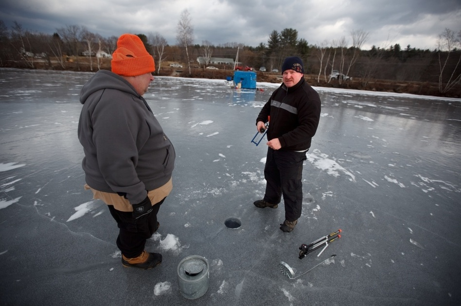 Dan Shaw of the Andover police department sets a line with friend Matt Snow of Belmont, N.H. (John W. Poole/NPR)