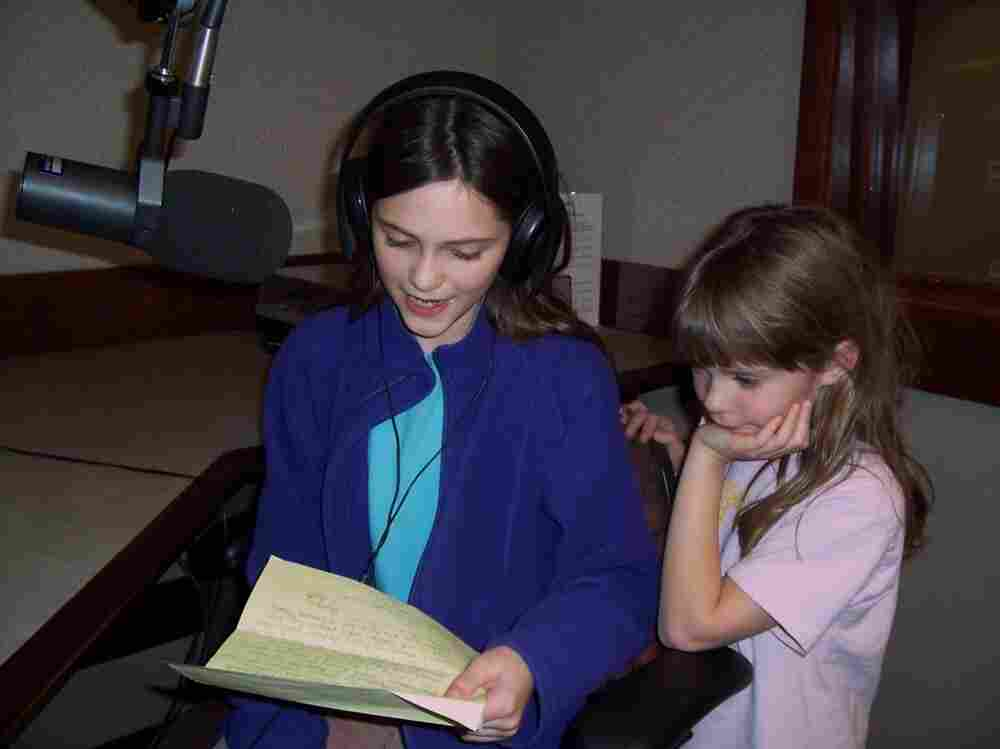 Liza reading her letter to WXXI while her sister Hannah looks on