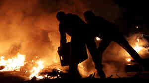 Two men try to extinguish a tire fire Thursday in Sitra, Bahrain, near the site of an opposition rally.Nightly clashes between riot police and protesters continued Thursday night nationwide.