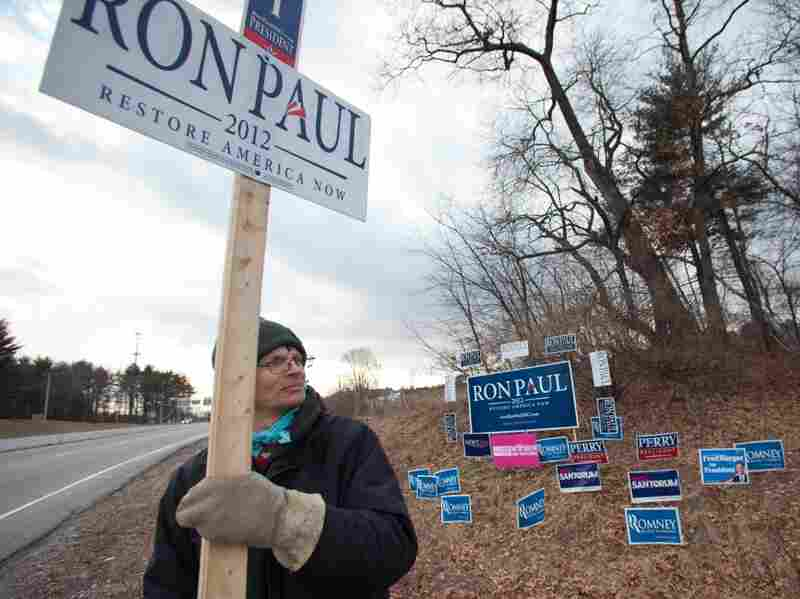 Warren Ojala of New Ipswich holds a sign supporting Ron Paul on the roadside in Manchester, NH.