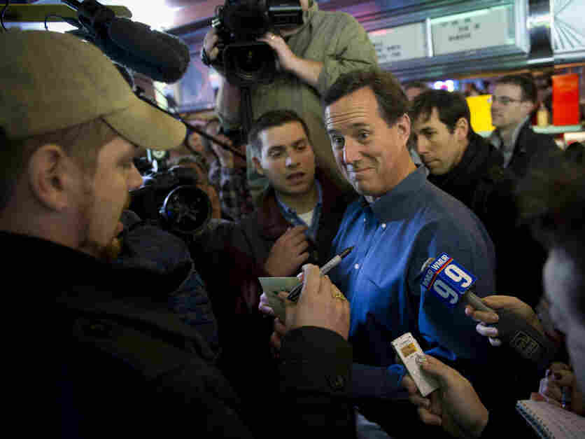Former Pennsylvania Sen. Rick Santorum talks with a customer while surrounded by news crews as he pays a visit to customers at the Tilt 'n Diner in Tilton, NH, on Jan. 5.