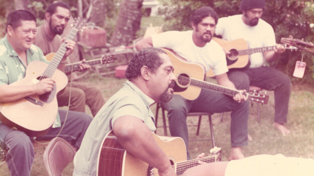"""Gabby Pahinui (center), playing in his family's backyard with (from left to right) Leland """"Atta"""" Isaacs, Philip Pahinui, Cyril Pahinui and Martin Pahinui. This photo is in the album insert for the 1972's Gabby."""
