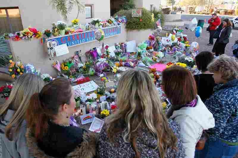 People pay their respects at a makeshift memorial outside Giffords' Tucson office a day after the shooting.