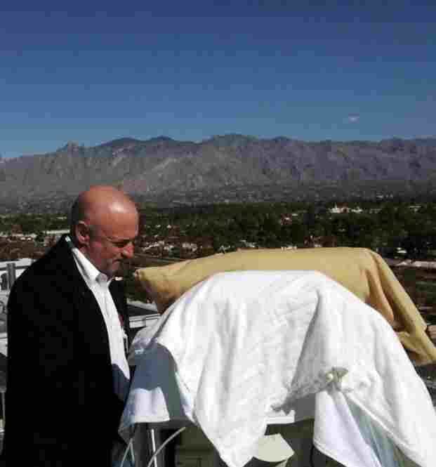 Kelly stands over his wife's hospital bed on a deck outside University Medical Center on Jan. 20.