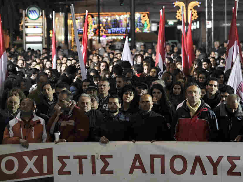 "Greek protesters gather behind a banner reading ""no to lay offs."""