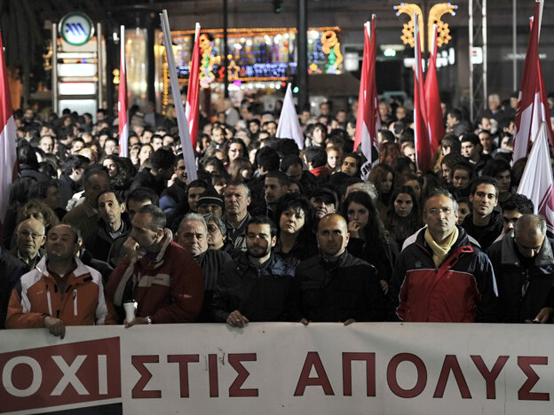 """Greek protesters gather behind a banner reading """"no to lay offs."""""""