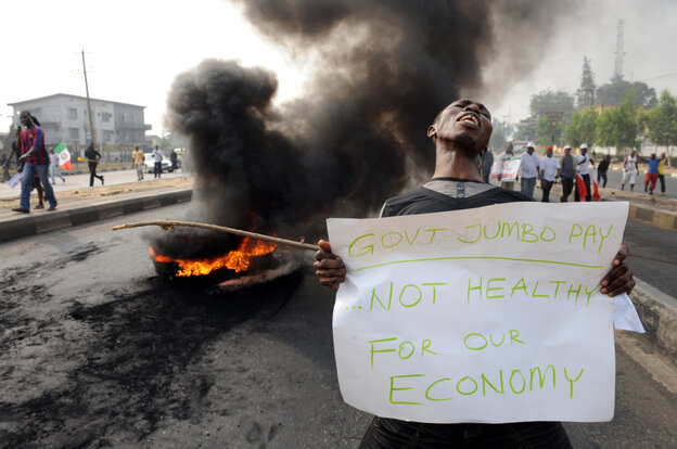 A man carries a placard beside a bonfire during Monday's demonstration against soaring petrol prices following government's decision to abolish decades-old fuel subsidies.