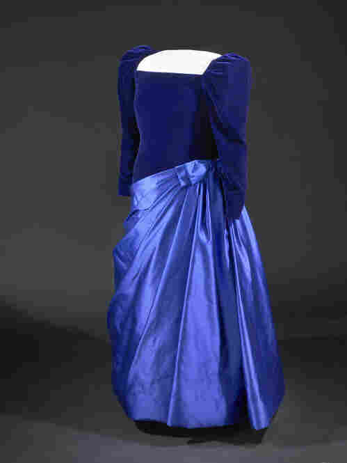 Barbara Bush's dark blue velvet and satin 1989 inaugural gown combines a velvet bodice with an asymmetrical draped satin skirt. The matronly gown was designed by Arnold Scassi, and Bush wore her signature pearls and a purse by Judith Leiber to complete the look.