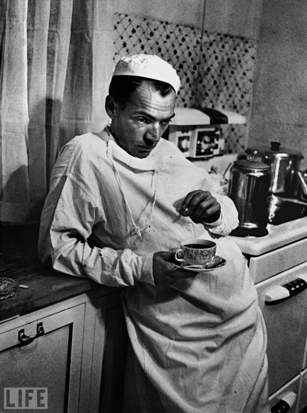 """Dr. Ernest Ceriani, the subject of a 1948 Life magazine story titled """"Country Doctor,"""" pauses after a long surgery."""