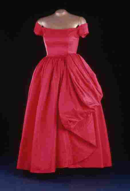 Mamie Eisenhower's red evening gown was designed by Nettie Rosenstein and worn to a 1957 state dinner at the British Embassy. The silk damask gown is noted for its small cap sleeves and included a matching purse and shoes.