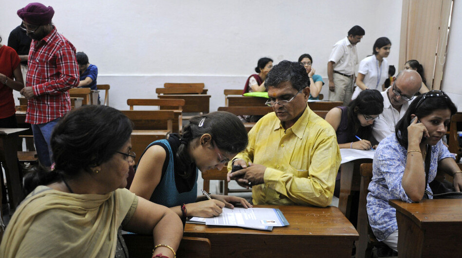 Parents help their children fill out applications at Delhi University's Shri Ram College of Commerce in New Delhi, India, on June 16. The College of Commerce is considered one of the most difficult to get into.
