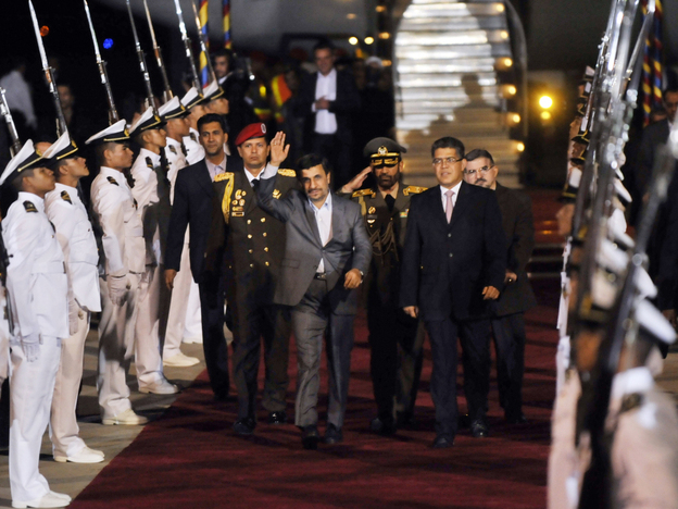 Iranian President Mahmoud Ahmadinejad waves as he is welcomed by Venezuelan Vice President Elias Jaua (at right, wearing glasses and tie) at the airport in Caracas on Sunday. Ahmadinejad is on a five-day tour aimed at shoring up ties in Latin America.