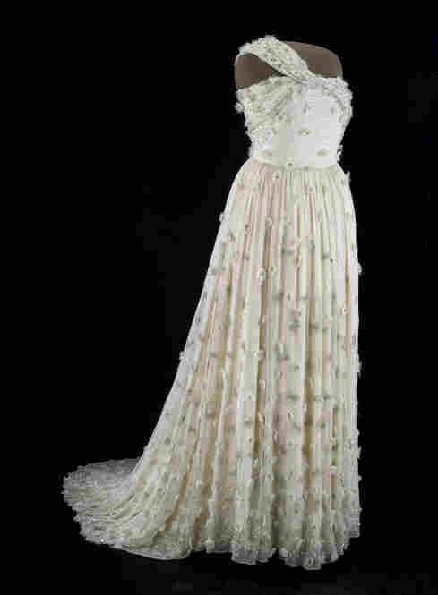 Michelle Obama's 2009 inaugural gown, designed by Jason Wu, echoes her trademark style. The one-shouldered gown is crafted from white silk chiffon with small details such as organza flowers and Swarovski crystal centers. In a video at the Smithsonian, she says an inaugural gown, in particular, puts us right in the moment.