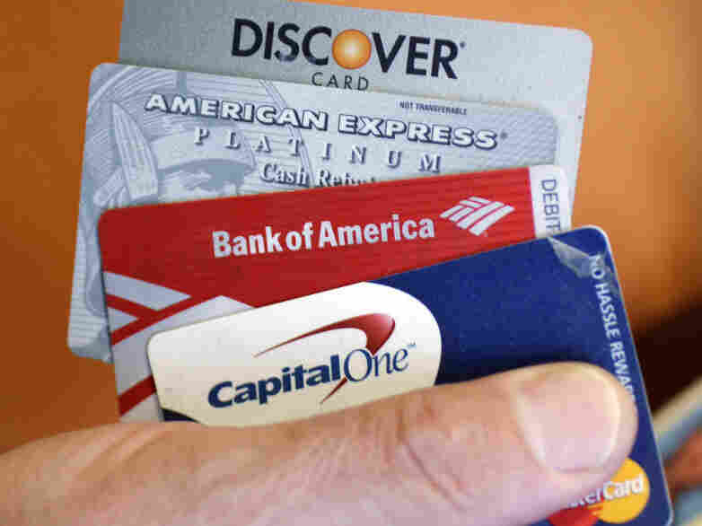 Steve Wheelock holds up his Discover Card along with his American Express, Bank of America and Capital One Visa credit cards in San Francisco, Wednesday, June 22, 2011. Discover Financial Services said Thursday, June 23, its second-quarter profit more than tripled as customers used their cards more and got better about making payments on time.