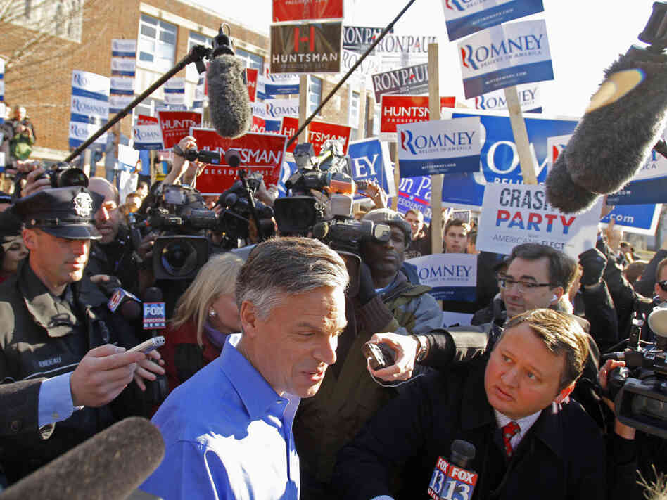 Former Utah Gov. Jon Huntsman makes his way through the media as he leaves a polling station in Manchester, N.H., on Tuesday. He's one of the candidates young Mormons are often asked about as they proselytize.